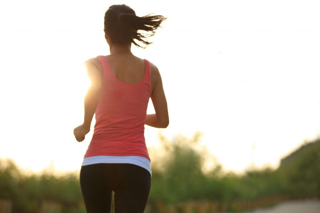 fitness woman jogging at sunrise mountain driveway