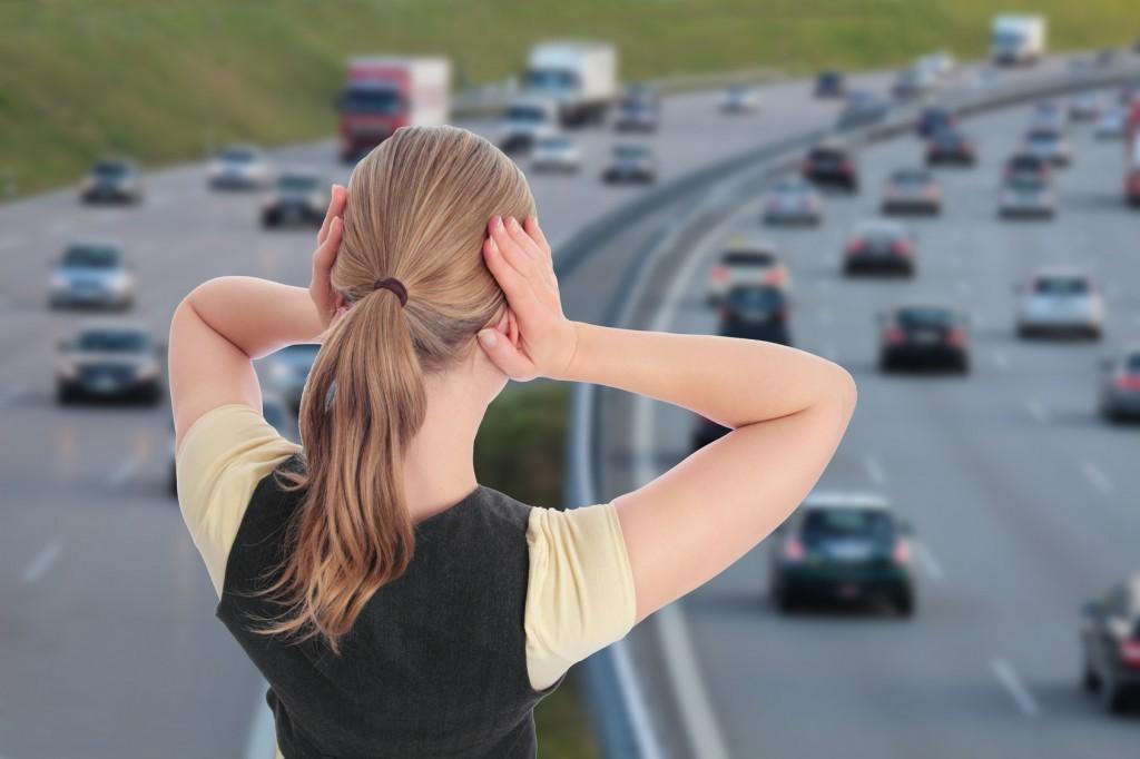 Frau mit Haenden an Ohren vor Autobahn